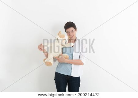 Crazy young woman is biting a plush toy or teddy bear.