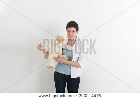 Frustrated attractive young woman biting a plush toy or teddy bear with a snarl and frown of anger.