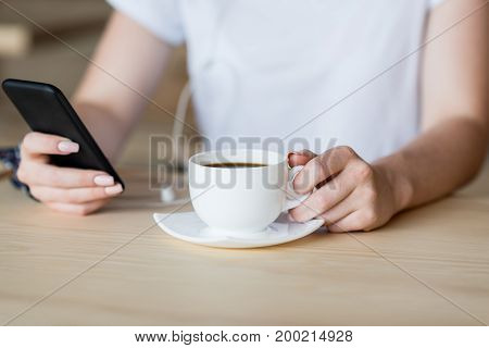Smartphone And Cup Of Coffee In Female Hands
