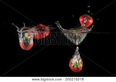 Strawberries splashing into water on a black background