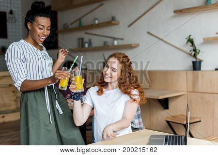 beautiful smiling multiethnic girls clinking glasses with juice in cafe