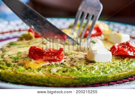 Close up tasty home made omelette with spinach, cheese and tomatoes