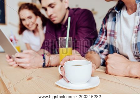 close-up partial view of young friends drinking coffee and juice while using digital tablet in cafe