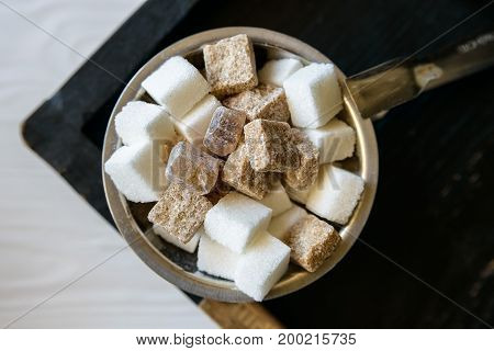 Close up sugar bowl with lumps of white and brown sugar in restaurant