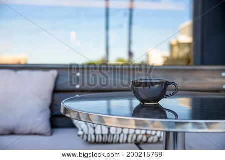 Closeup image of a black tea cup on table of outdoors restaurant