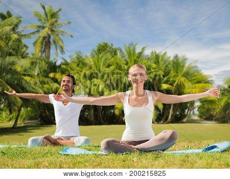 fitness, sport, yoga and people concept - happy couple meditating in lotus pose outdoors over exotic natural background with palm trees