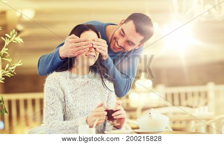 people, surprise and dating concept - happy couple drinking tea at cafe or restaurant