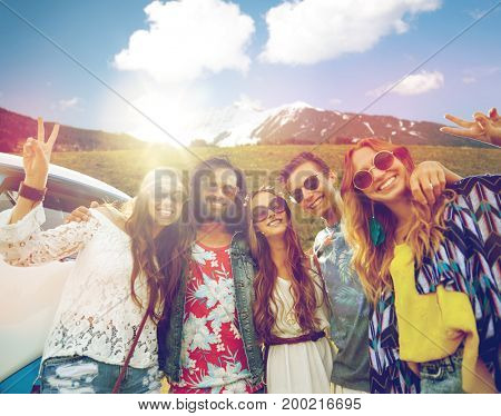 summer holidays, road trip, travel and people concept - smiling young hippie friends at minivan car showing peace hand sign over alps mountains background