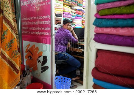 Dhaka, bangladesh, august 2017- a cloth seller at his own store looking behind with putting hand on mouth at near motijhil area, Dhaka, bangladesh