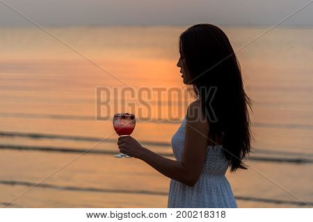 Beautiful woman enjoy and relax with holding cocktail at sunset beach