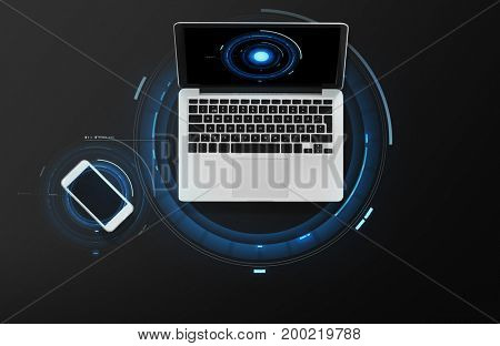 electronics and technology concept - laptop computer and smartphone top view