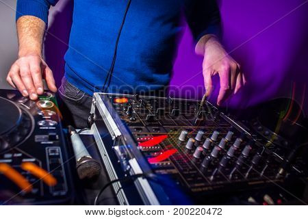 DJ's hands at the music mixer at a party - playing some fine songs for the guests (color toned image)