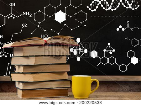 Digital composite of Books on Desk foreground with blackboard graphics of science formula drawings diagrams
