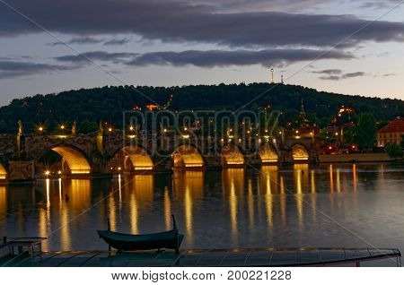 View on highlighted Carlos Bridge at night. with reflection in the water.