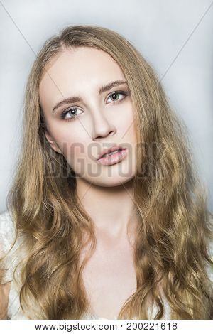 Portrait with emotional daring audacious face of young blonde beautiful girl with nude make up and long healthy shiny hair, looking and posing on white background