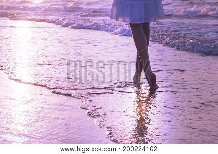 A girl is walking along Crete island coastline at the sunset. Lilac toning.