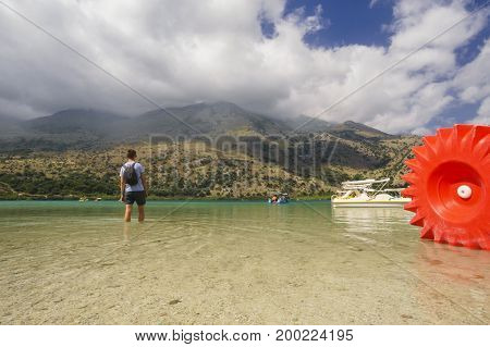 Man standing with back in mountain lake kournas on Crete island Greece