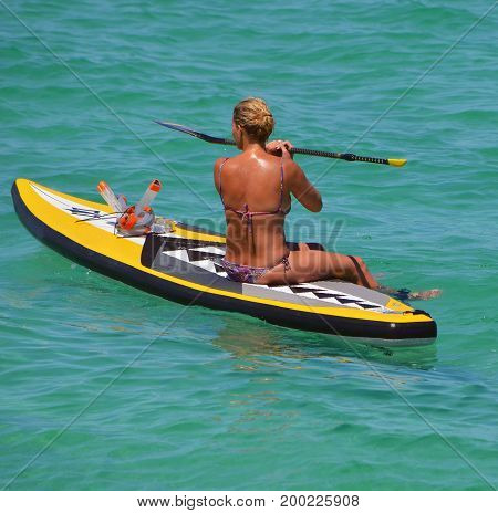 Woman resting on a paddle board off Southpointe Park Beach at the southern end of Miami Beach,Florida.