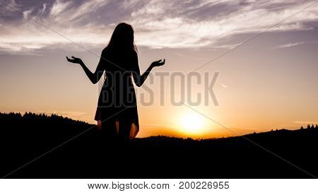 Silhouette of girl with long hair and dress during sunset. The girl is indecisive. Decision.