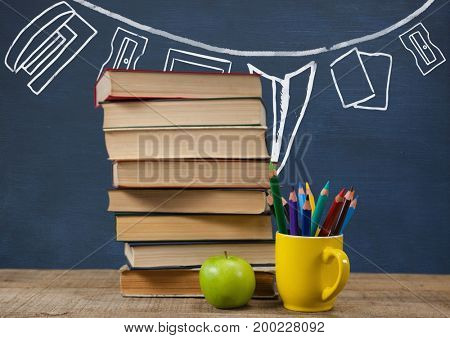 Digital composite of Books on the table against blue blackboard with graphics