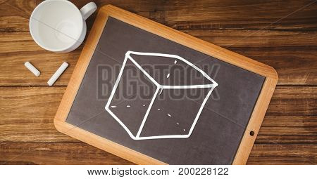 Digital composite of cube on blackboard