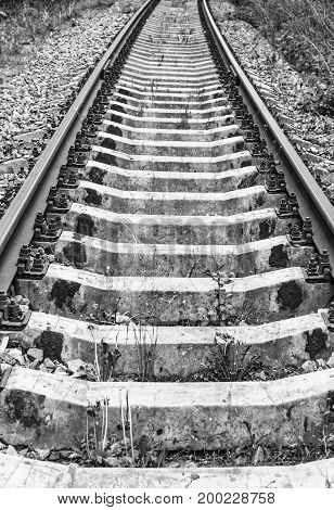 Rails and sleepers in black and white at day
