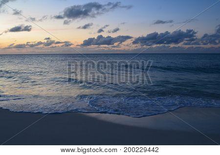 Aruba's setting sun with waves rolling ashore.