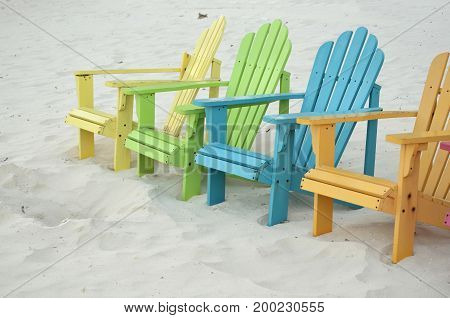 Bright pastel colored beach chairs on a white sand beach.