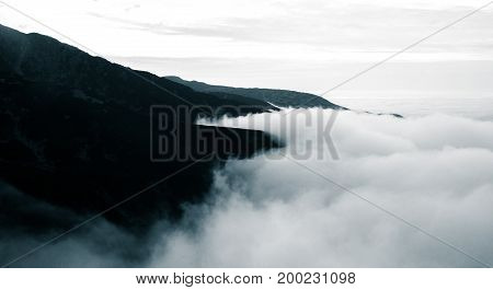 A Beautiful Monochromatic Mountain View With Rising Clouds