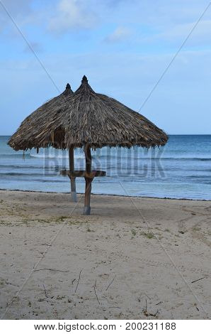 Deserted pair of Palapas on Eagle Beach in Aruba.