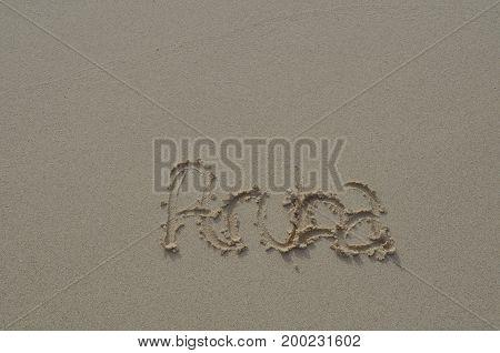 Smooth damp beach sand with Aruba written in it.