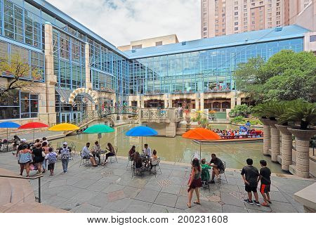 SAN ANTONIO TEXAS - AUGUST 7 2017: Tourists on the San Antonio River Walk near Rivercenter Mall. This interconnected network of walkways on the San Antonio River is a popular tourist destination.