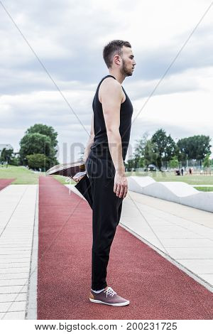 Young athlete in black sports clothing preparing for training or for competitions on a red running track in summer