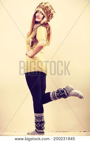 Winter fashion. Happy young woman in full length wearing fashionable wintertime clothes fur cap woolen warm socks posing