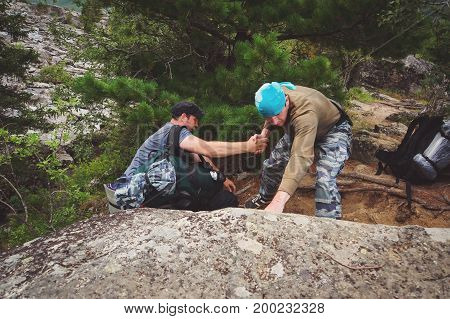 A man helps a friend with a large backpack to climb the stone. Camper helps another to climb the rock. Mutual aid Hiking in the wild. Collective work and mutual assistance when you work in a team. Friendly Hand on the High Mountain Hike. Men Helping Other