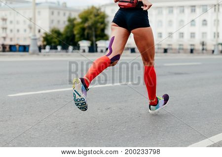 woman running city marathon in compressing socks and kinesiotape hamstring