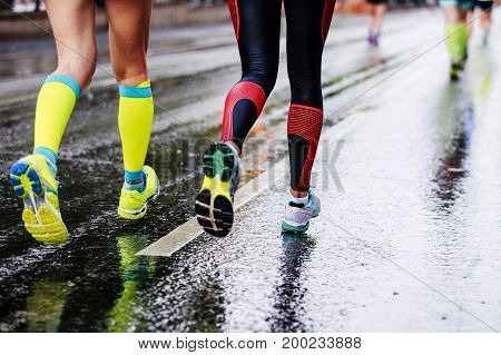 feet two girls athletes running on wet street urban marathon