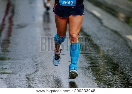 feet athlete woman in compression socks running urban road
