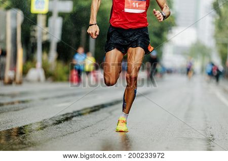 leader athlete runner running city marathon in rain