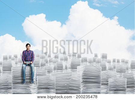 Young man in casual clothing sitting on pile of documents with cloudly skyscape on background. Mixed media.