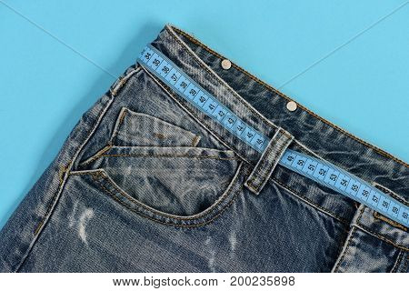Top Part Of Denim Trousers Isolated On Blue Background
