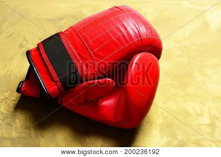 Boxing gloves in red color. Professional box and strong fight concept. Sport equipment on golden pattern background. Pair of leather boxing sportswear.