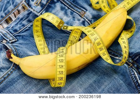Mens denim pants crotch with banana imitating male genitals. Health and male sexuality concept. Banana wrapped with yellow measure tape on jeans selective focus. Jeans zipper and pocket close up.