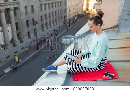 Attractive And Stylish Girl Sits On The Roof Of The House In The Old Town And Reads The E-book. She