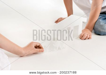 partial view of kids holding paper family and house models isolated on white