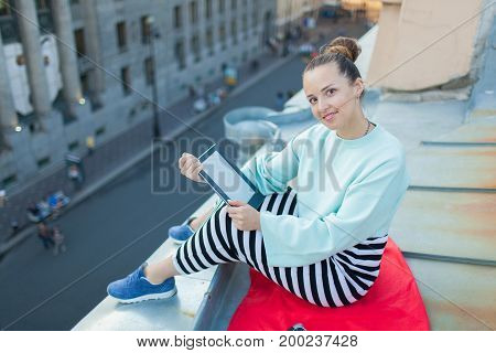 Attractive And Stylish Girl Sits On The Roof Of The House In The Old Town And Reads The E-book