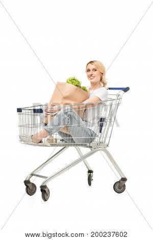 smiling woman with paper bag in hands sitting in shopping cart isolated on white