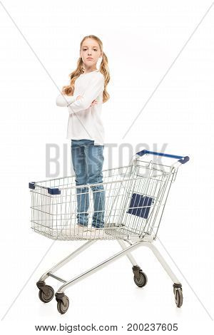 little girl with arms crossed standing in shopping cart isolated on white