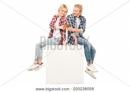side view of smiling couple clinking glasses of juice isolated on white