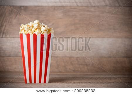 Popcorn In Red And White Cardboard On Wooden Table.